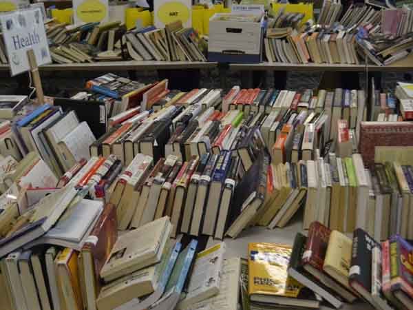 Library staff and volunteers have arranged piles of books into easy-to-peruse categories.