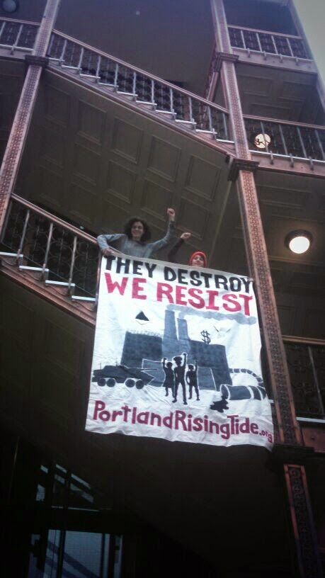 Members of Portland Rising Tide drop banner in Portland City Hall