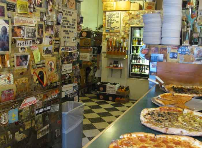 Behind pizza pies being offered by the slice, a jammed bulletin board conveys the feeling of neighborhood.