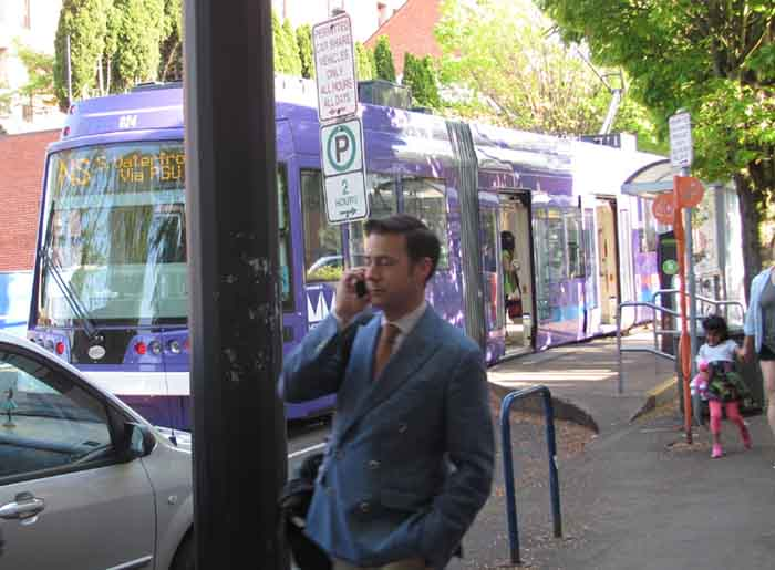 A cellphone user is barely distracted by the Portland Streetcar.