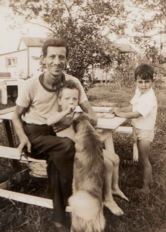 A friendly canine is curious about Jon, whom my father is holding.  Mason is on their right.
