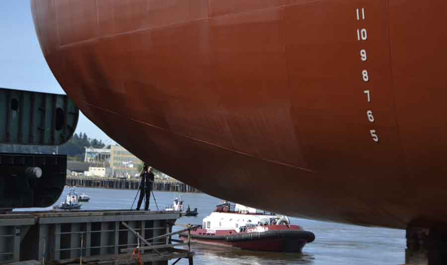 The mammoth barge dwarfs a cameraman and tugboat below.
