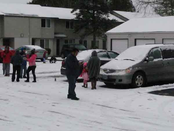 Apartment residents bring their children outside to revel in less than an inch of snow on the ground.